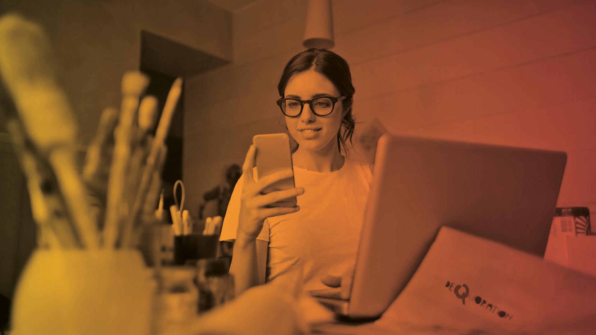 Junge Fachkraft schaut ins konzentriert auf das ihr Smartphone.